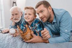 Μικρό παιδί, ο πατέρας και ο παππούς του που βρίσκονται στο κρεβάτι με τη σφαίρα και το γάντι πυγμαχίας και την προσοχή α μπέιζ-μ στοκ φωτογραφία