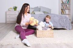 Μικρό παιδί, παιχνίδι μητέρων με τα παιχνίδια στο καλάθι στην κρεβατοκάμαρα Στοκ φωτογραφία με δικαίωμα ελεύθερης χρήσης