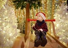 Μικρό παιδί που έχει τη διασκέδαση και που κάνει τη φωτογραφία στην εγκατάσταση Χριστουγέννων με τα φω'τα στο υπόβαθρο Αγορές οικ στοκ εικόνες