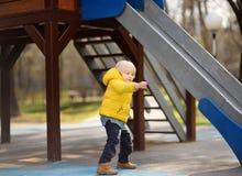 Μικρό παιδί που έχει τη διασκέδαση στην υπαίθρια παιδική χαρά την ημέρα άνοιξης ή πτώσης Στοκ φωτογραφία με δικαίωμα ελεύθερης χρήσης