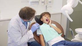 Μικρό παιδί που έχει tootache, καθμένος στην οδοντική καρέκλα κατά τη διάρκεια της εξέτασης δοντιών απόθεμα βίντεο