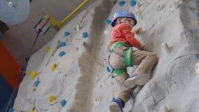 Μικρό παιδί που αναρριχείται σε έναν τοίχο βράχου σε ένα λουρί εσωτερικό Έννοια της αθλητικής ζωής απόθεμα βίντεο