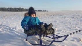 Μικρό παιδί που απολαμβάνει έναν γύρο ελκήθρων Μωρό στο έλκηθρο Τα παιδιά παίζουν υπαίθρια στο χιόνι Εύθυμες χειμερινές διακοπές  φιλμ μικρού μήκους