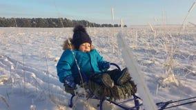 Μικρό παιδί που απολαμβάνει έναν γύρο ελκήθρων Μωρό στο έλκηθρο Τα παιδιά παίζουν υπαίθρια στο χιόνι Εύθυμες χειμερινές διακοπές  απόθεμα βίντεο