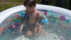 Μικρό παιδί που απολαμβάνει το λούσιμο θερινής ημέρας στη λίμνη του απόθεμα βίντεο