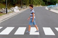 Μικρό παιδί που διασχίζει στο δρόμο στοκ εικόνα