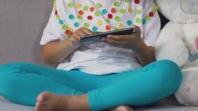 Μικρό παιδί που επισύρει την προσοχή στο smartphone δίπλα στη teddy αρκούδα, ηλεκτρονική στη καθημερινή ζωή απόθεμα βίντεο