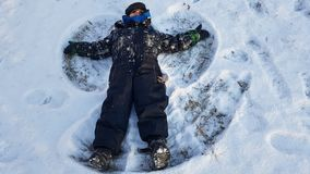 Μικρό παιδί που κάνει snowangel Στοκ Εικόνες