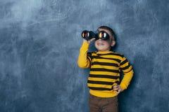 Μικρό παιδί που κοιτάζει μέσω των διοπτρών σε ένα σκούρο μπλε υπόβαθρο με μια ευτυχή στάση προσώπου στοκ φωτογραφία με δικαίωμα ελεύθερης χρήσης