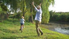 Μικρό παιδί που μαθαίνει να οδηγά το ποδήλατο με τη βοήθεια από τον μπαμπά της στην υπαίθρια φύση υποβάθρου και το μικρό ποταμό απόθεμα βίντεο