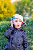 Μικρό παιδί που μιλά στο κινητό τηλέφωνο υπαίθρια στοκ φωτογραφία με δικαίωμα ελεύθερης χρήσης