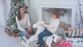 Μικρό παιδί που οδηγά το ξύλινο άλογο λικνίσματος ενώ η συνεδρίαση mom του δίπλα στην εστία Χριστουγέννων στοκ εικόνες