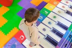 Μικρό παιδί που παίζει ένα μουσικό πιάνο οργάνων παιδιών Στοκ Φωτογραφίες