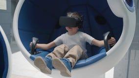 Μικρό παιδί που παίζει την εικονική πραγματικότητα σε μια κινούμενη διαλογική καρέκλα απόθεμα βίντεο