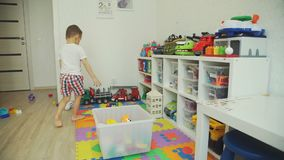 Μικρό παιδί που παίρνει τα παιχνίδια σε ένα πλαστικό κιβώτιο απόθεμα βίντεο