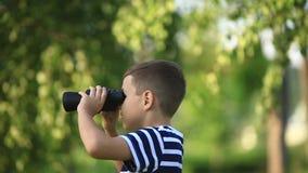 Μικρό παιδί που περπατά στο πάρκο και που κοιτάζει μέσω των διοπτρών απόθεμα βίντεο