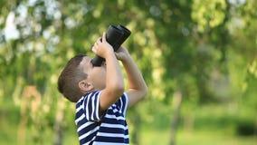 Μικρό παιδί που περπατά στο πάρκο και που κοιτάζει μέσω των διοπτρών φιλμ μικρού μήκους