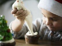 Μικρό παιδί που προσθέτει την τήξη σε ένα cupcake Στοκ φωτογραφία με δικαίωμα ελεύθερης χρήσης