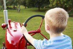 Μικρό παιδί που προσποιείται να οδηγήσει ένα παλαιό τρακτέρ Στοκ Εικόνες