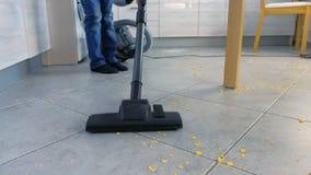 Μικρό παιδί που σκουπίζει το πάτωμα κουζινών με ηλεκτρική σκούπα Τακτοποιεί τις νιφάδες καλαμποκιού που διασκορπίζονται στο γκρίζ απόθεμα βίντεο