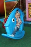 Μικρό παιδί που ταλαντεύεται σε ένα μπλε παιχνίδι υπό μορφή ψαριών στο Pla Στοκ εικόνες με δικαίωμα ελεύθερης χρήσης