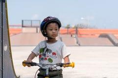 Μικρό παιδί που φορά τα κράνη που απελευθερώνουν το ποδήλατο στοκ εικόνες με δικαίωμα ελεύθερης χρήσης