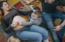 Μικρό παιδί που χαϊδεύει την κοιλιά της έγκυου μητέρας του στοκ εικόνες