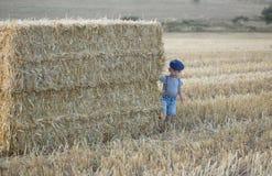 Μικρό παιδί σε έναν σωρό του σανού στοκ φωτογραφίες