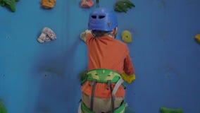 Μικρό παιδί σε ένα λουρί που αναρριχείται σε έναν τοίχο με τα πιασίματα φιλμ μικρού μήκους