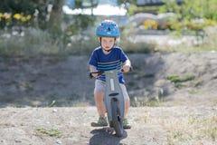 Μικρό παιδί σε ένα ποδήλατο Strider σε μια διαδρομή ρύπου που φορά το κράνος Στοκ φωτογραφία με δικαίωμα ελεύθερης χρήσης