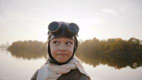 Μικρό παιδί στο εκλεκτής ποιότητας πειραματικό κοστούμι με το μαντίλι και γυαλιά που εξετάζουν τη κάμερα που καθιστά τα αστεία πρ απόθεμα βίντεο