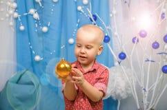 Μικρό παιδί στο ντεκόρ Χριστουγέννων που κρατά μια σφαίρα στοκ εικόνα