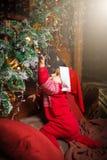 Μικρό παιδί σχετικά με τις διακοσμήσεις στο καπέλο Άγιου Βασίλη Στοκ Εικόνες
