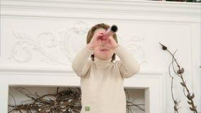 Μικρό παιδί χρησιμοποιώντας το ρόλο εγγράφου ως γυαλί κατασκόπων και έχοντας την πάλη ξιφών εγγράφου τυλίγματος με το mom του στοκ φωτογραφία