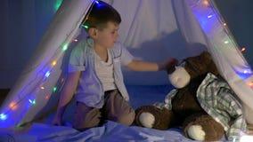 Μικρό παιχνίδι αγοριών με τη teddy αρκούδα στο ντεκόρ σκηνών με τη γιρλάντα στο σπίτι το βράδυ φιλμ μικρού μήκους