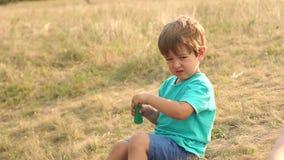 Μικρό παιχνίδι αγοριών με τις φυσαλίδες σαπουνιών στο ηλιοβασίλεμα φιλμ μικρού μήκους
