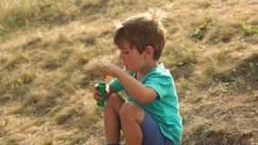 Μικρό παιχνίδι αγοριών με τις φυσαλίδες σαπουνιών στο ηλιοβασίλεμα απόθεμα βίντεο