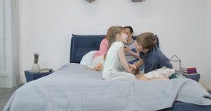 Μικρό παιχνίδι αδελφών και αδελφών στο κρεβάτι γονέων ενώ η μητέρα και ο πατέρας χρησιμοποιούν την έξυπνη έννοια πρωινού τηλεφωνι φιλμ μικρού μήκους