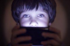 Μικρό παιχνίδι παιδιών σε ένα smartphone Στοκ Εικόνα