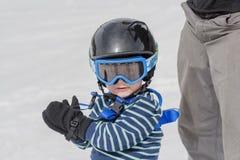 Μικρό παιδί έτοιμο να κάνει σκι ακίνδυνα με το κράνος και το λουρί Στοκ φωτογραφία με δικαίωμα ελεύθερης χρήσης