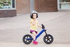 Μικρό παιδί αγοριών κοριτσιών που οδηγά ένα ποδήλατο ποδηλάτων ισορροπίας στο κράνος στο δρόμο Στοκ Φωτογραφία