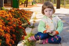Μικρό παιδί γύρω από τα κρεβάτια λουλουδιών στο πάρκο Στοκ Εικόνες