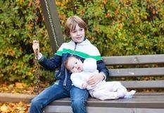 Μικρό παιδί και η νεογέννητη αδελφή μωρών του στην ταλάντευση Στοκ Εικόνα