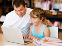 Μικρό παιδί και ο πατέρας του με το lap-top στοκ εικόνες