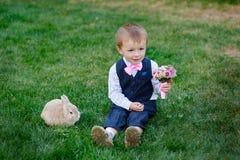 Μικρό παιδί με μια ανθοδέσμη των λουλουδιών και μια συνεδρίαση κουνελιών στη χλόη Στοκ φωτογραφία με δικαίωμα ελεύθερης χρήσης