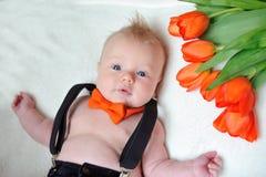 Μικρό παιδί με μια πορτοκαλιά πεταλούδα και μια ανθοδέσμη των λουλουδιών Στοκ φωτογραφία με δικαίωμα ελεύθερης χρήσης