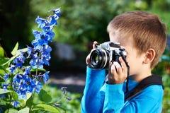 Μικρό παιδί με την αναδρομική κάμερα που βλασταίνει τα μακρο λουλούδια Στοκ Φωτογραφία