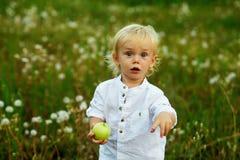 Μικρό παιδί με την πράσινη Apple στη φύση Στοκ Φωτογραφία