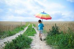 Μικρό παιδί με τη μεγάλη ομπρέλα που περπατά μακριά επάνω Στοκ Φωτογραφία