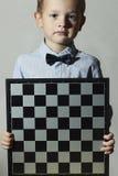 Μικρό παιδί με τη σκακιέρα Fashion Children Λίγο παιδί μεγαλοφυίας Ευφυής Στοκ φωτογραφία με δικαίωμα ελεύθερης χρήσης